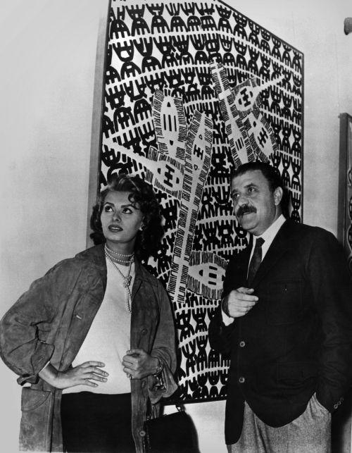 Carlo Cardazzo con Sofia Loren davanti a un'opera di Giuseppe Capogrossi, Galleria del Naviglio, Milano, anni '50. Archivio Galleria del Cavallino, Venezia